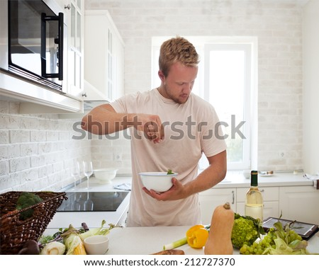 Handsome man cooking at home preparing salad in kitchen - stock photo