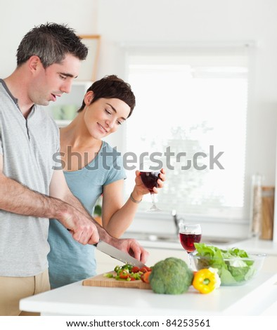 Handsome Man cutting vegetables while is woman is watching in a kitchen