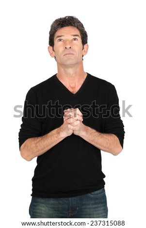Handsome man doing different expressions in different sets of clothes: praying - stock photo