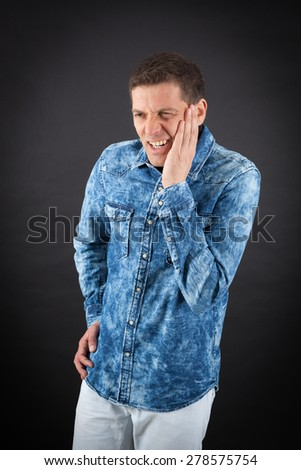 Handsome man doing different expressions in different sets of clothes: toothache - stock photo