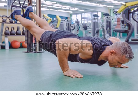Handsome man doing hard suspension training with fitness straps in a fitness center. Healthy and sporty lifestyle concept. - stock photo