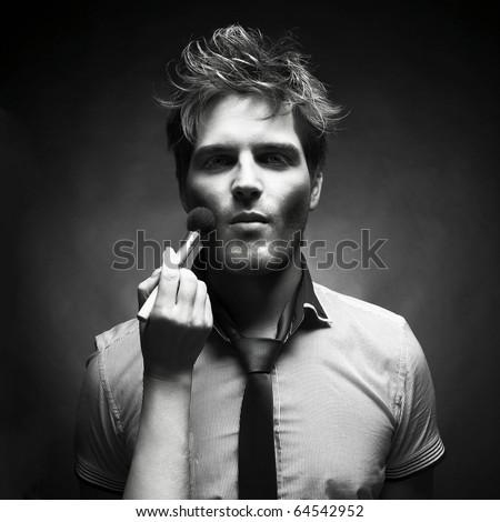 Handsome man doing makeup for fashion photography studio - stock photo