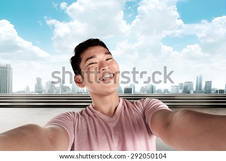 Handsome man doing selfie with cityscape background - stock photo