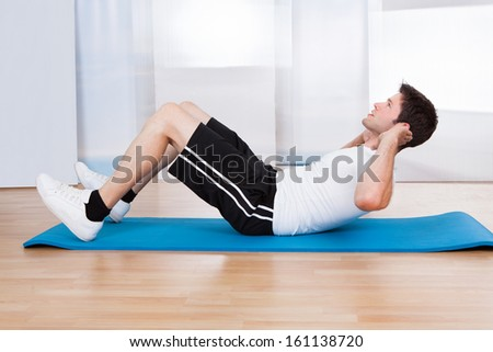 Handsome Man Doing Sit-ups On A Blue Exercise Mat - stock photo