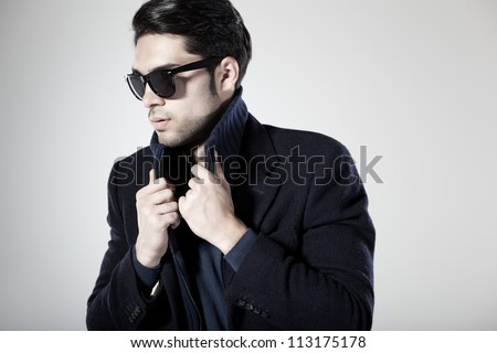handsome man dressed casual with sun-glasses posing in the studio - stock photo