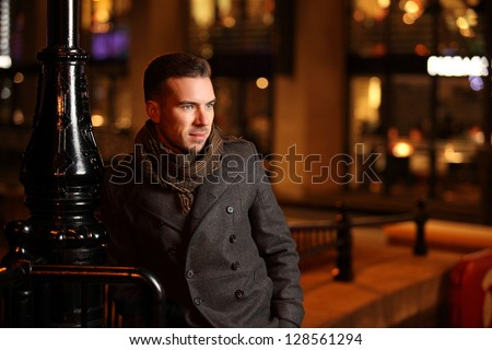 handsome man dressed in grey bouble breasted coat leaning against lantern