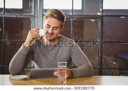 Handsome man drinking coffee and looking at tablet at coffee shop - stock photo