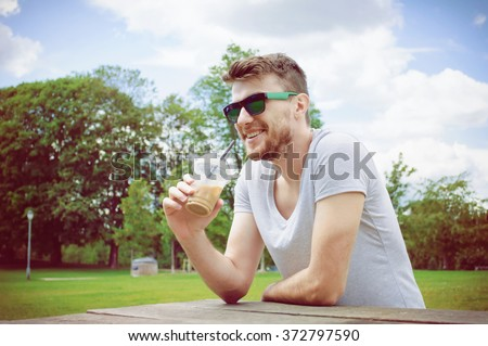 Handsome man drinking coffee in park - stock photo