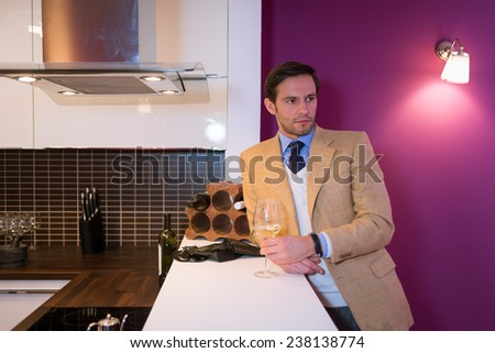 Handsome man, drinking white wine at home - stock photo