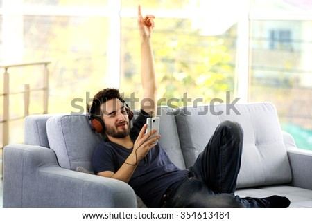 Handsome man emotionally listens music with headphones on grey sofa in the room - stock photo