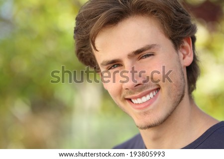Handsome man face with a white perfect smile with a green background