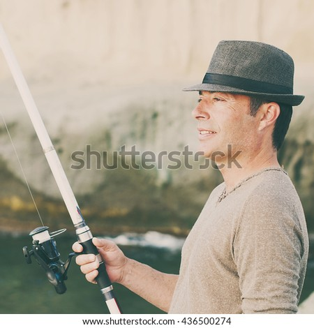Handsome man fishing during his day off, selective focus and square image