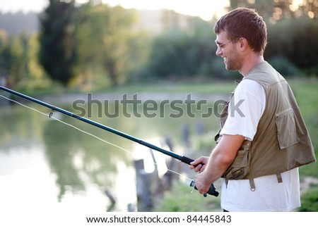 Handsome man fishing. Shot against clear blue sky. selective focus, shallow DOF. - stock photo