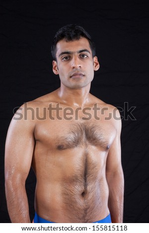 Handsome man from India standing shirtless, with hair on his chest and well defined muscles, looking at the camera  - stock photo
