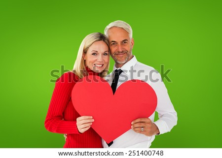Handsome man getting a heart card form wife against green vignette - stock photo