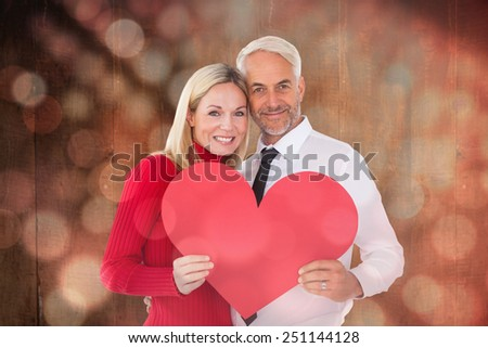 Handsome man getting a heart card form wife against light circles on black background - stock photo