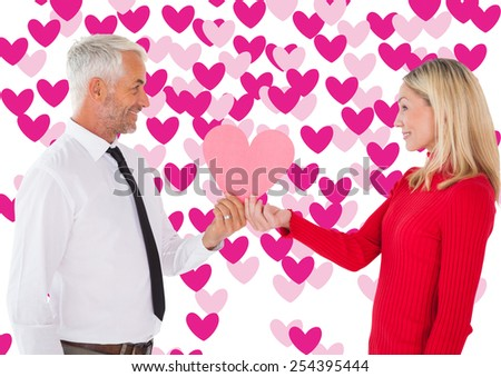 Handsome man getting a heart card form wife against valentines day pattern - stock photo