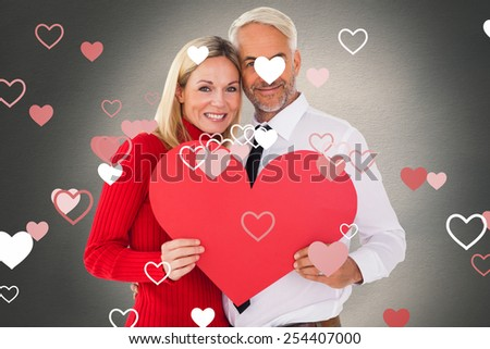 Handsome man getting a heart card form wife against white background with vignette - stock photo