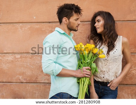Handsome man giving a bouquet of tulips young woman
