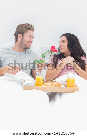 Handsome man giving a rose to his wife during breakfast in their bed - stock photo