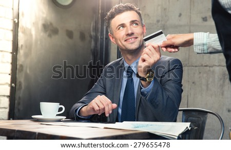 Handsome man giving bank card to waiter in cafe - stock photo