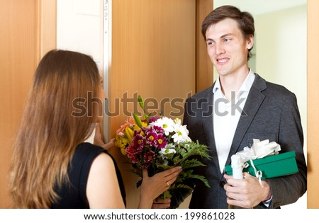 Handsome man giving gifts to woman at home door