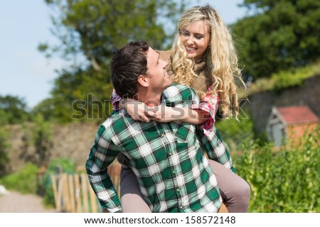 Handsome man giving his girlfriend a piggyback ride in their garden - stock photo