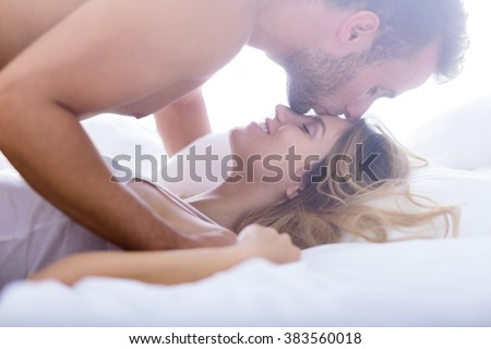 Handsome man giving kiss in his girlfriend's forehead - stock photo
