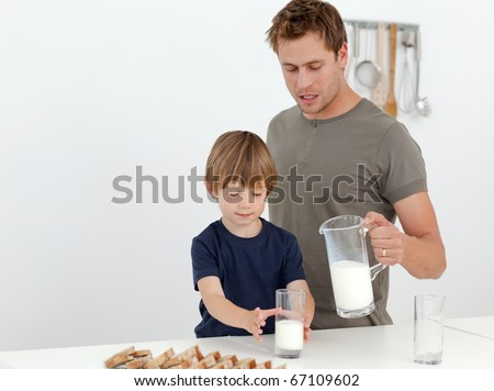 Handsome man giving milk to his son standing in the kitchen - stock photo