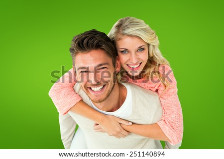 Handsome man giving piggy back to his girlfriend against green vignette - stock photo