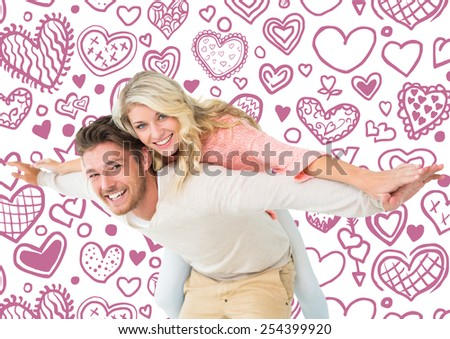 Handsome man giving piggy back to his girlfriend against heart pattern - stock photo