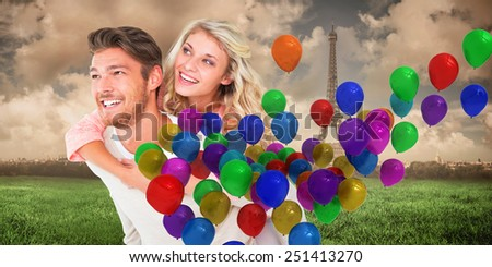 Handsome man giving piggy back to his girlfriend against paris under cloudy sky - stock photo