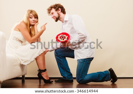 Handsome man giving pretty unhappy bored woman candy bunch flowers. Young boyfriend with present gift kneeling in front of girlfriend. - stock photo