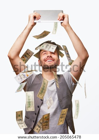 Handsome man happy and surprised with hundred dollars rain falling from his tablet PC. - stock photo