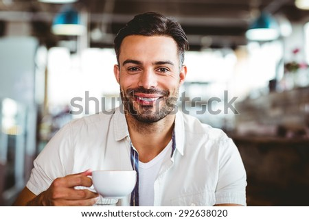 Handsome man having a coffee at the cafe - stock photo