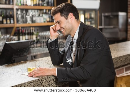 Handsome man having a whiskey and a phone call in a pub - stock photo