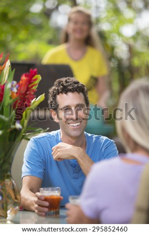 Handsome man having drinks with friend outdoors - stock photo