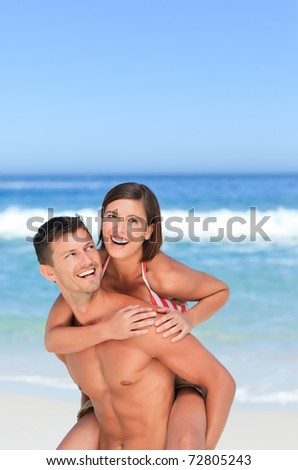 Handsome man having wife a piggyback on the beach - stock photo