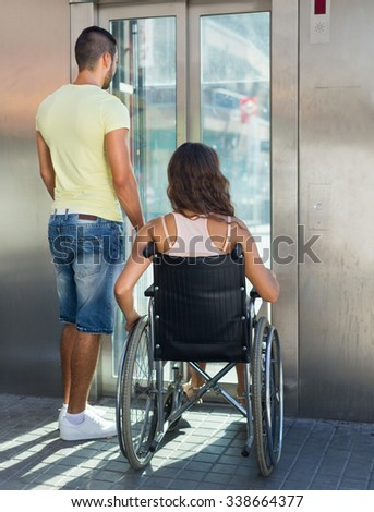 Handsome man helping handicapped girlfriend at outdoor elevator
