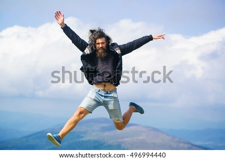 Handsome man hipster with beard and moustache in warm coat and denim shorts jumps on mountain top on cloudy sky