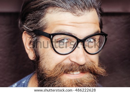 Handsome man hipster with long beard moustache and graying hair in glasses smiles on dark wall