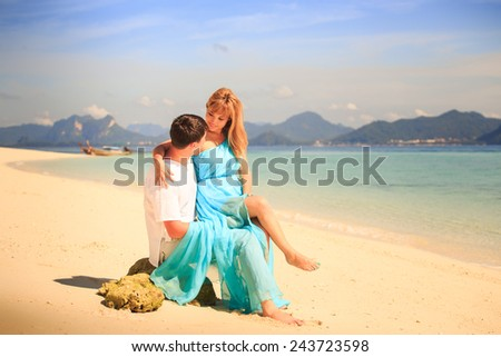 handsome man hold on his knees beautiful blonde woman in elegant dress with blue sea and mountains on background