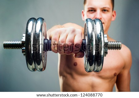 handsome man holding a dumbbell in front - stock photo