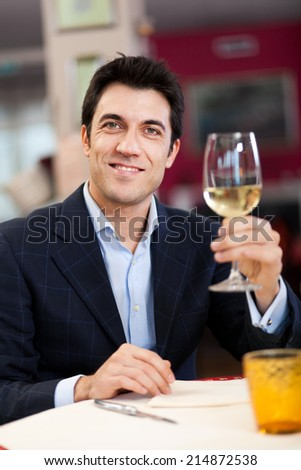 Handsome man holding a glass of wine - stock photo