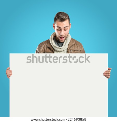 handsome man holding an empty cardboard over blue background  - stock photo