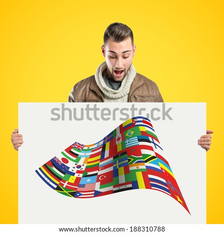 handsome man holding an empty cardboard over yellow background  - stock photo