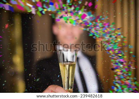 Handsome man holding flute of champagne against colour curve - stock photo