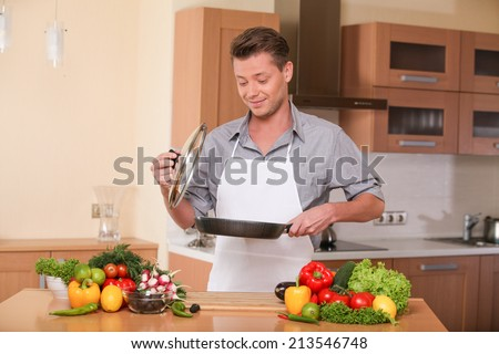 handsome man holding frying pan for fresh vegatebles. guy preparing healthy food at kitchen - stock photo