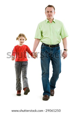Handsome man holding his daughter by hand while they walking together