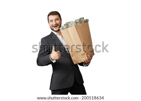handsome man holding paper bag with money and showing thumbs up. isolated on white background - stock photo